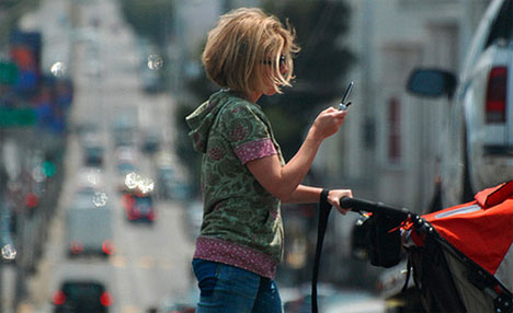 A Zombie texting while crossing the street with a baby stroller